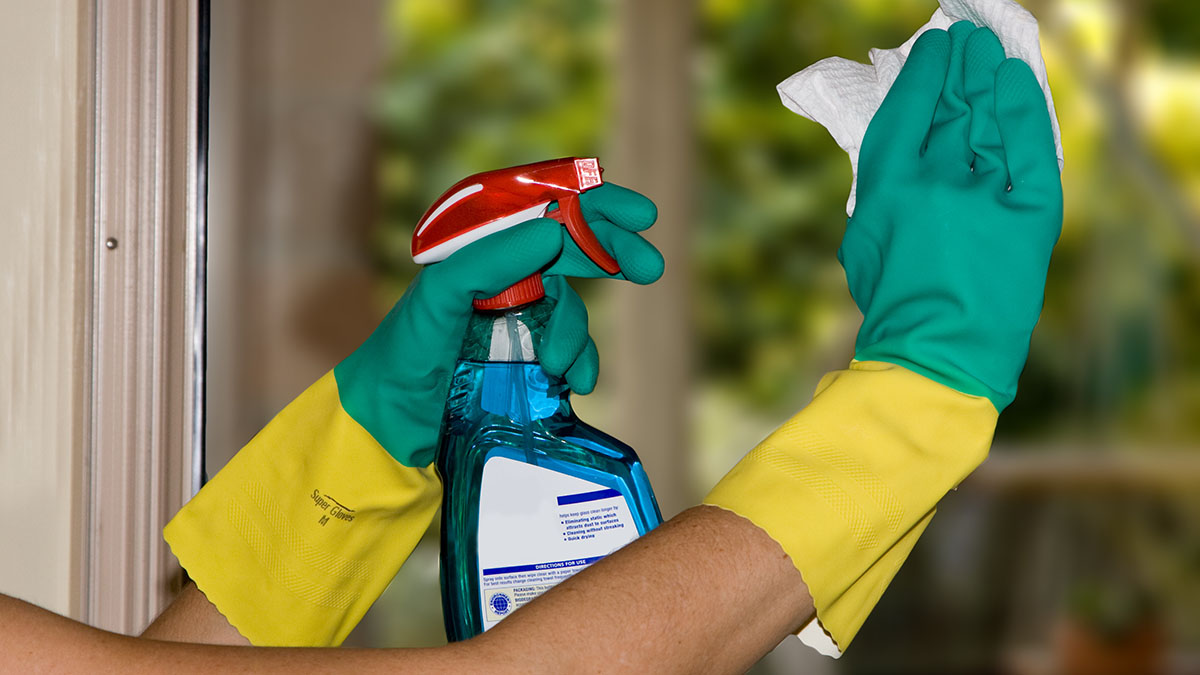 Cleaning windows with kitchen towels and detergent spray